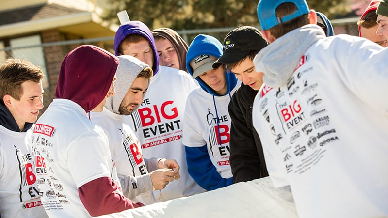 A group of student volunteers wearing t-shirts for the Big Event with sponsor logos on back