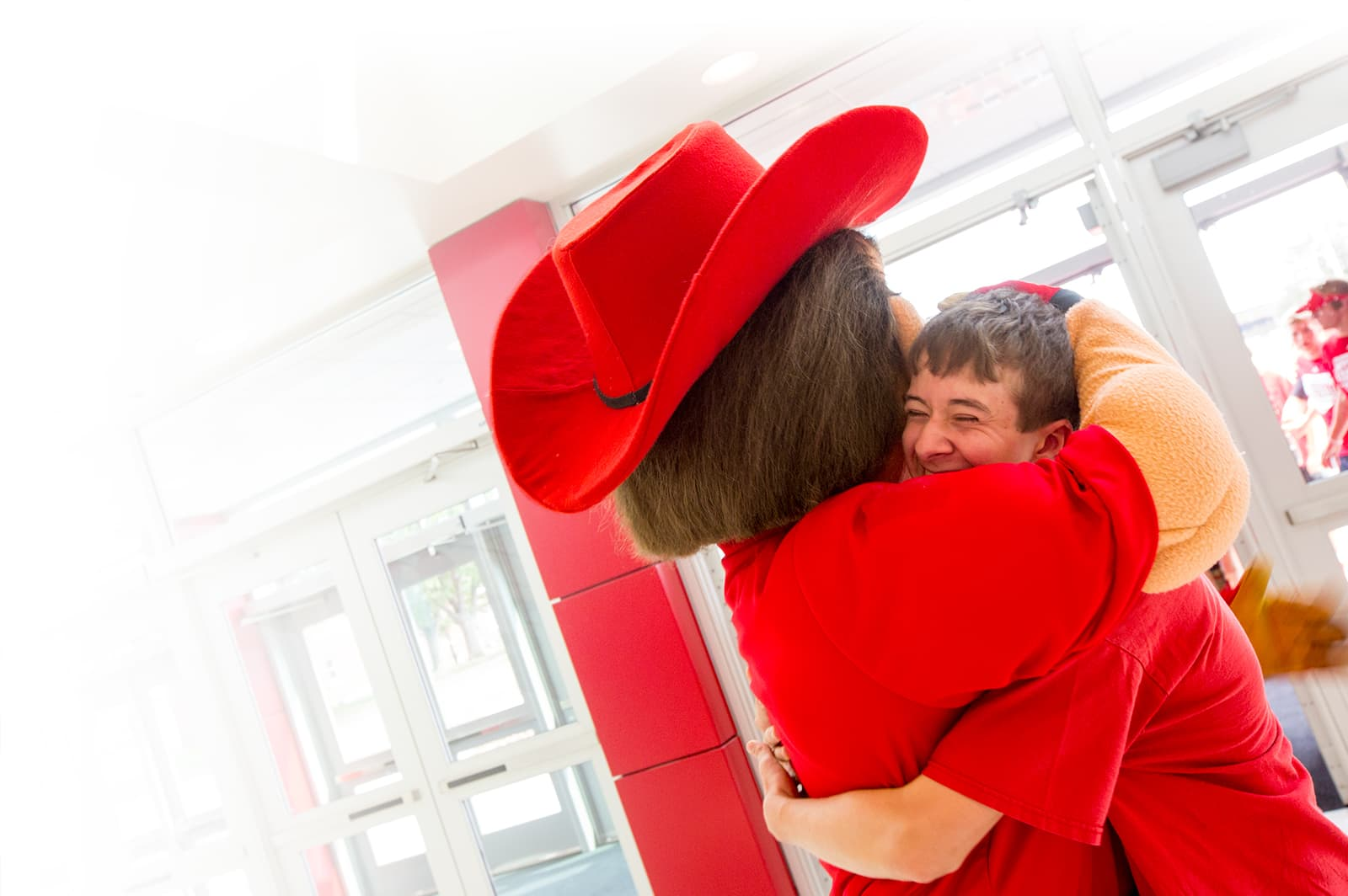 University of Nebraska–Lincoln mascot, Herbie Husker, gives a fan a hug
