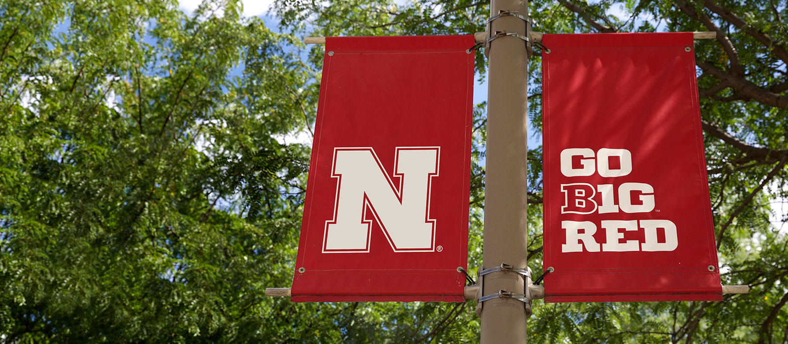 Red flags on flagpoles around campus feature the Nebraska 'N' and Go Big Red graphics